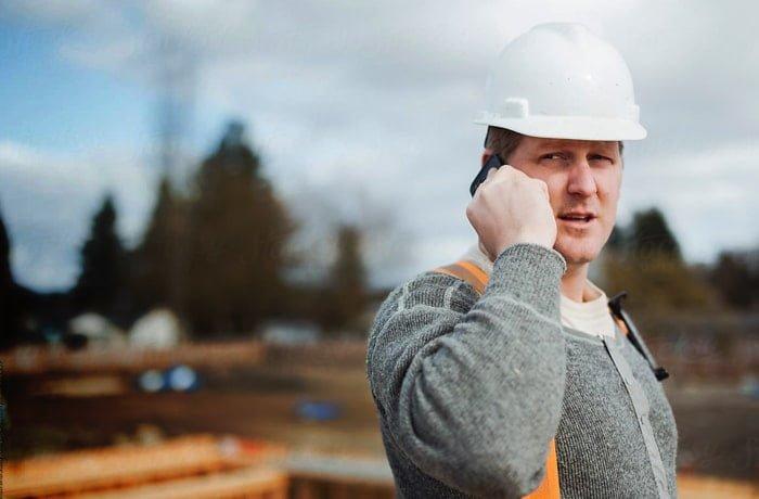 Udenlandsk byggevikarer der står og snakker i telefon med beskyttelseshjelm på hovedet